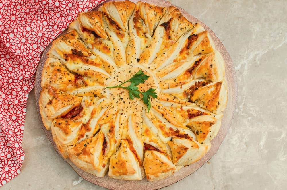 A puff pastry pizza on round tray on a marble counter with a red print cloth behind it.