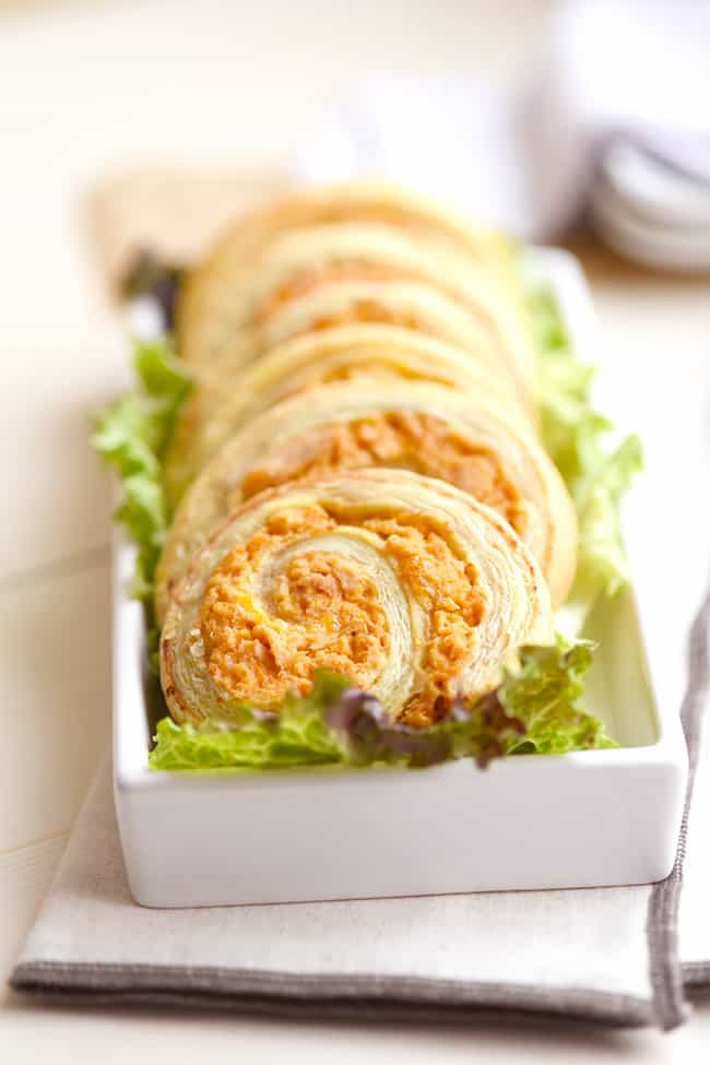 A rectangle white dish with a row of buffalo chicken pinwheels laying on leaf lettuce.