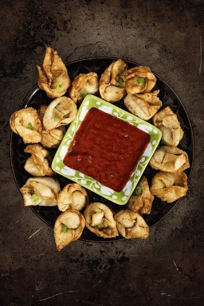 A black plate of crunchy wontons arranged around a square bowl of dipping sauce.
