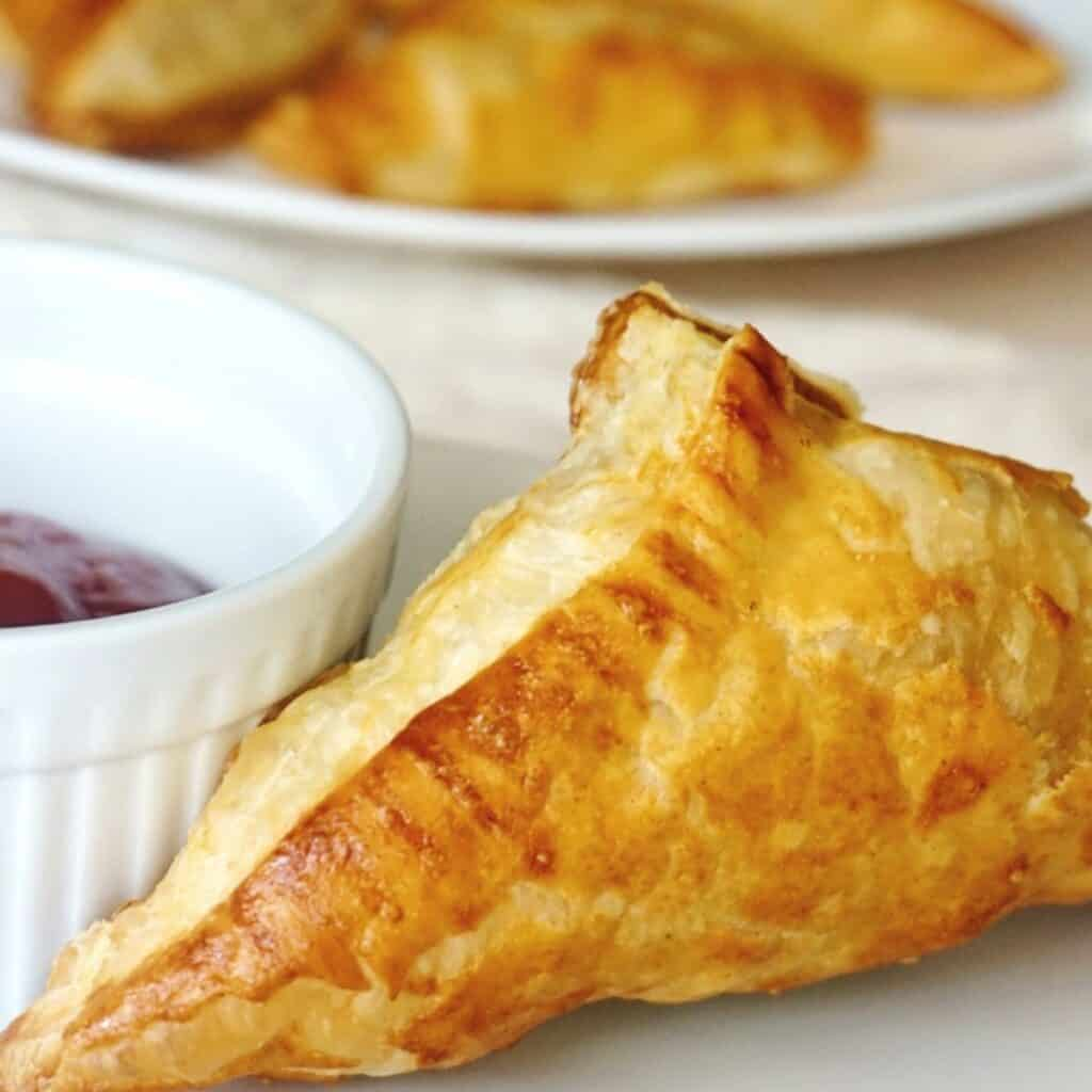 A close up of a chicken curry puffed pastry sitting next to a small bowl of sauce.
