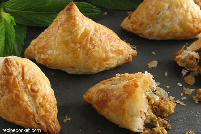 Three whole and one half puff pastry triangles filled with a chicken mixture with a green leaf garnish.