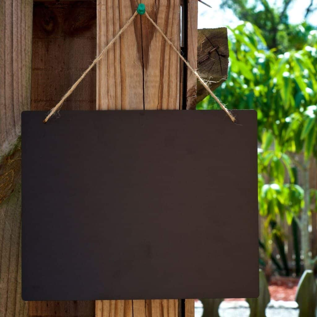 Chalkboard hanging at an outdoor party.