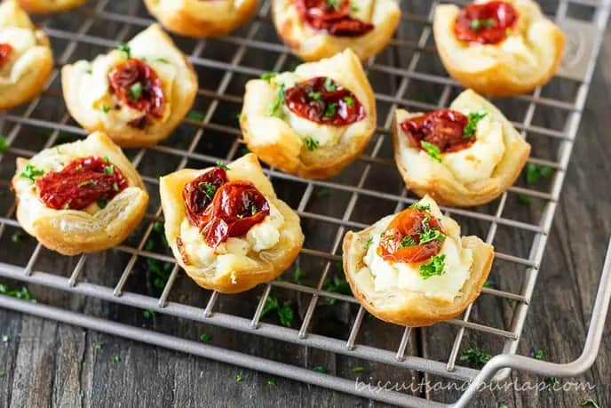 A wire rack wit goat cheese appetizers with roasted tomatoes on top.