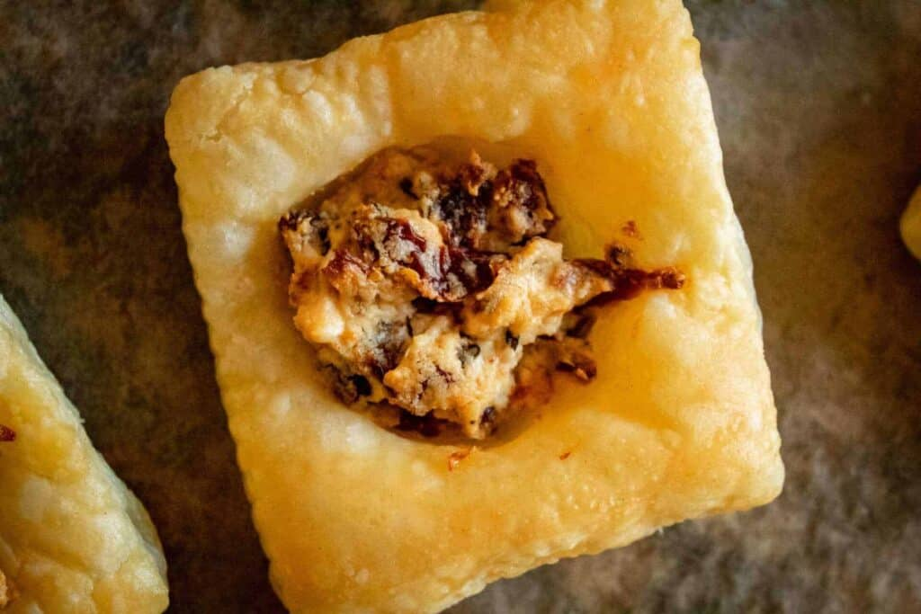 Close up of a puff pastry square filled with goat cheese and sundried tomatoes.