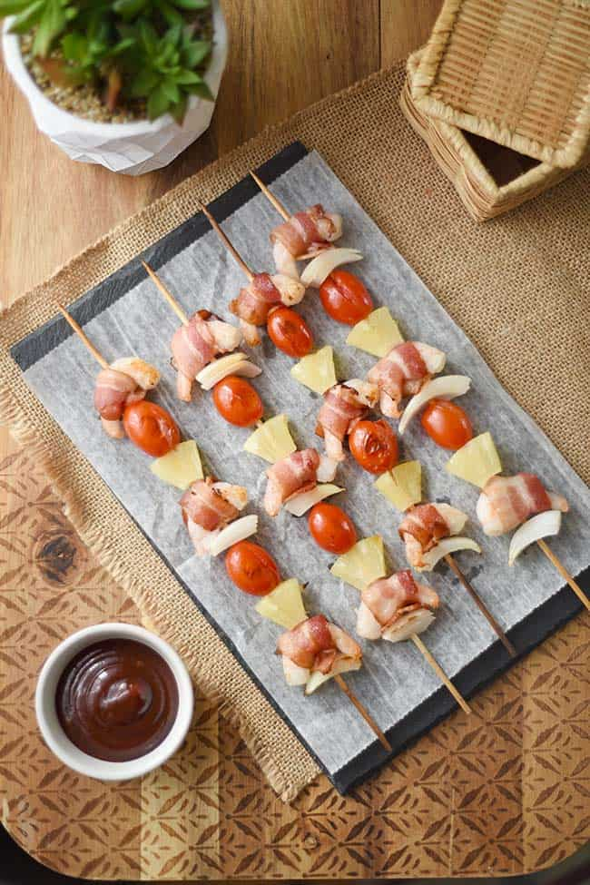 Skewers of bacon wrapped shrimp with pineapple and grape tomatoes.