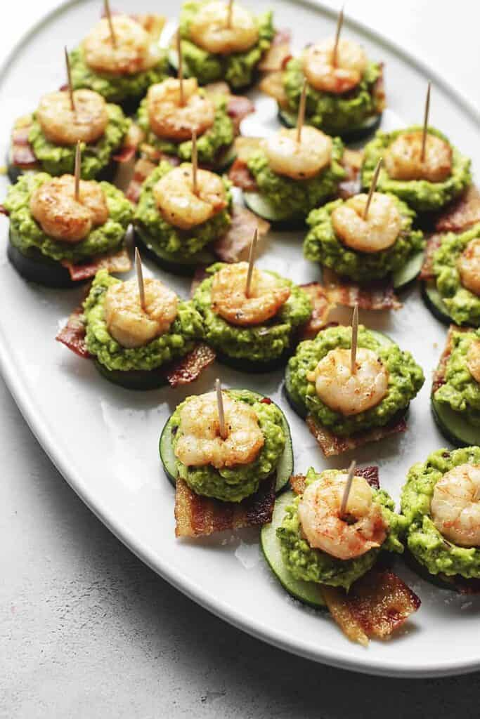 Cucumber, bacon, guacamole, and shrimp layered with a toothpick through them on a white platter.