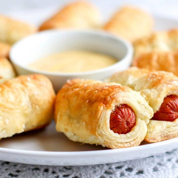 Puff pastry wrapped hot dogs on a white plate with a small white bowl of sauce in the middle.