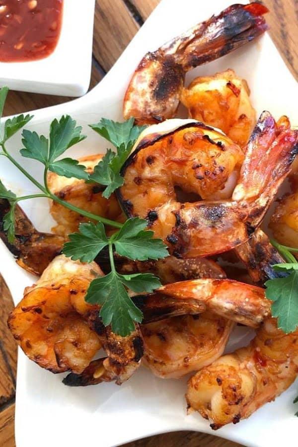 Pile of Korean BBQ shrimp on white plate with green leafy garnish.