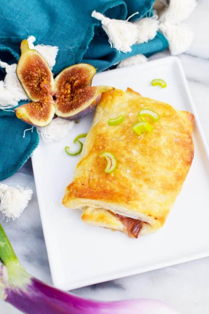 A caramelized onion & fig pastry laying on a square white tray with two halves of a fig laying next to it.