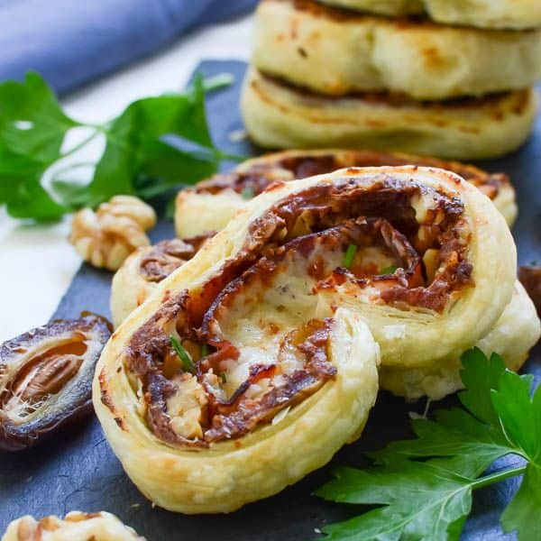 A close up of a prosciutto and date palmier and laying on a stack of them and green leaf garnish with a half of a date on a black cutting board.