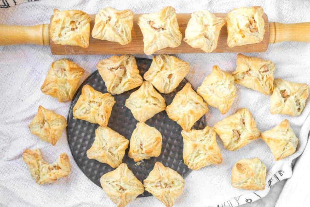 Potato puff appetizers sitting on a rolling pin and round silver baking pan all on a white cloth.