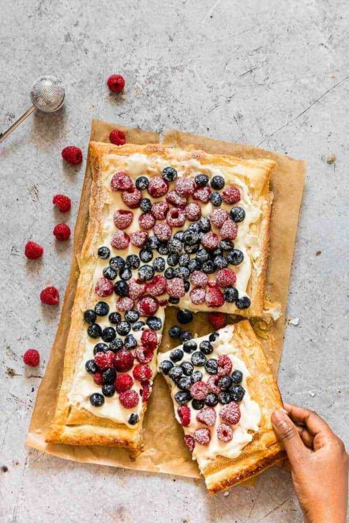Blueberry and raspberry tart laying on brown paper on concrete with someone holding a piece and raspberry laying beside it.
