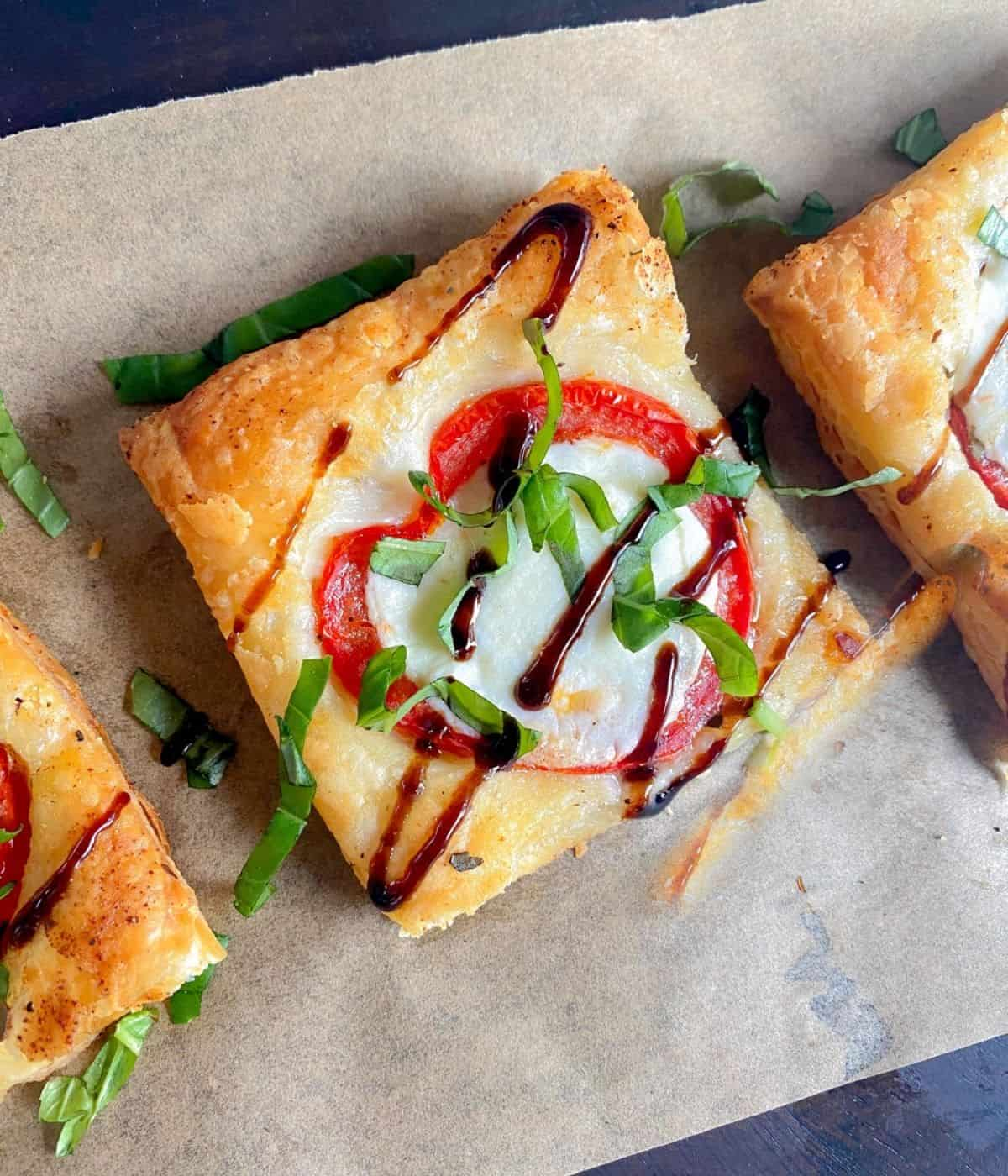 Puff pastry pizza with basil, mozzarella cheese and tomatoes.