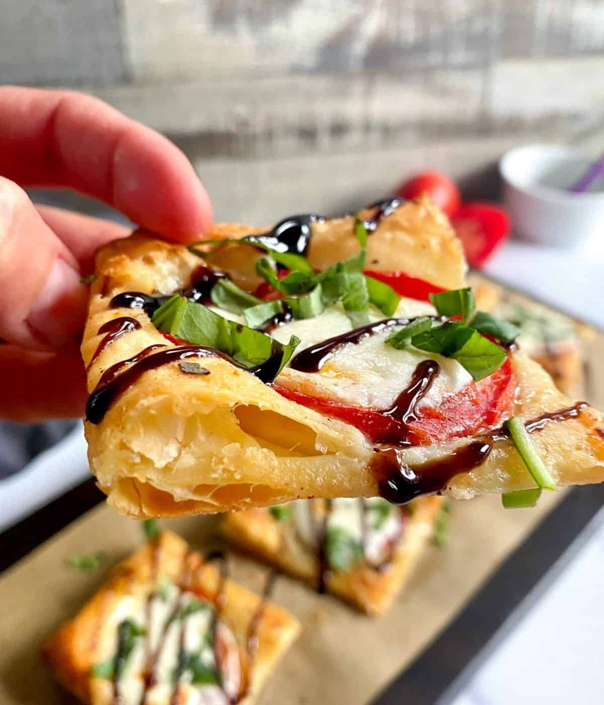 Close up of puff pastry pizza slice in hand.