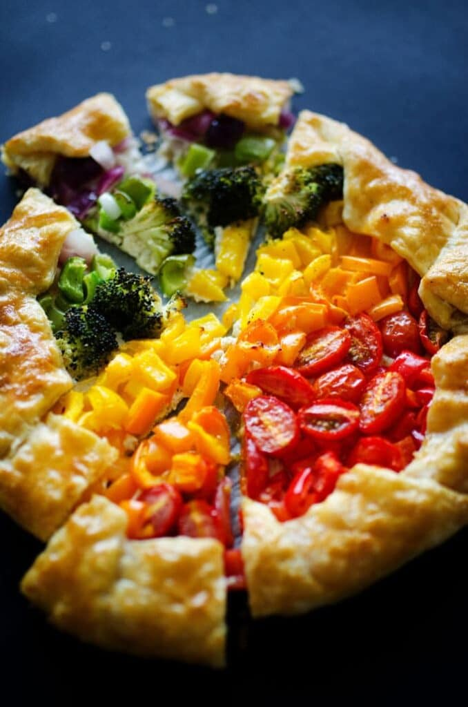 Top view of a tart with cherry tomatoes, yellow peppers and broccoli.