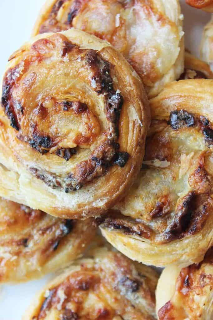 A stack of puff pastry pinwheels with bacon and cheese inside.