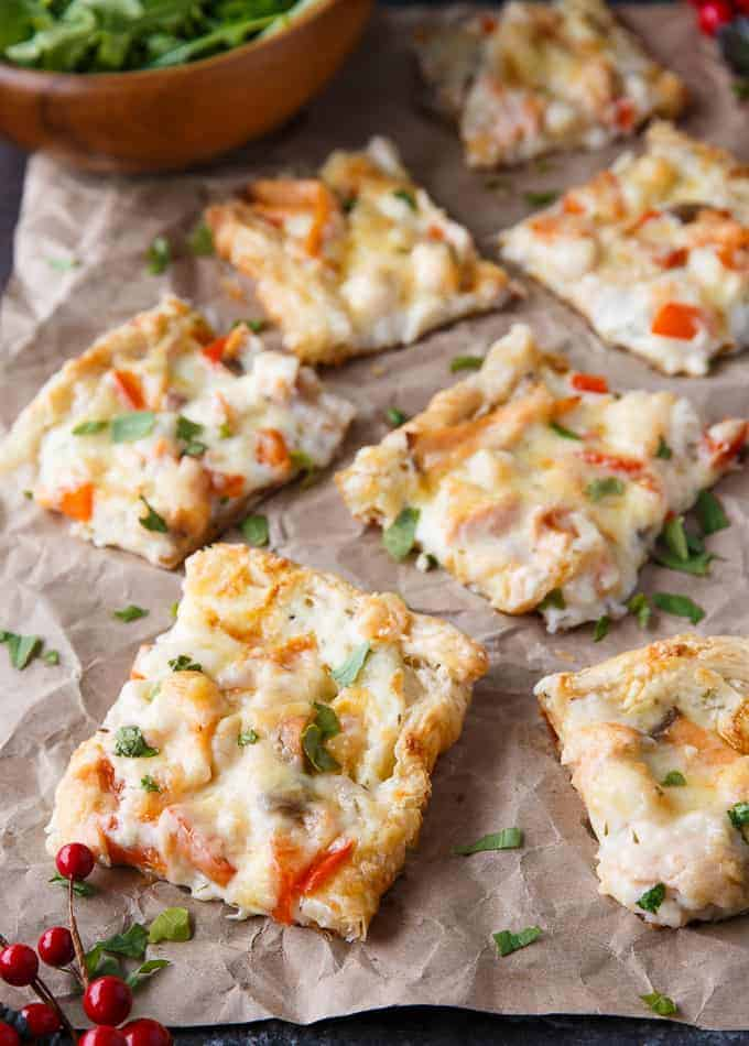 Squares of seafood pizza on a crumbled brown paper with a green garnish.