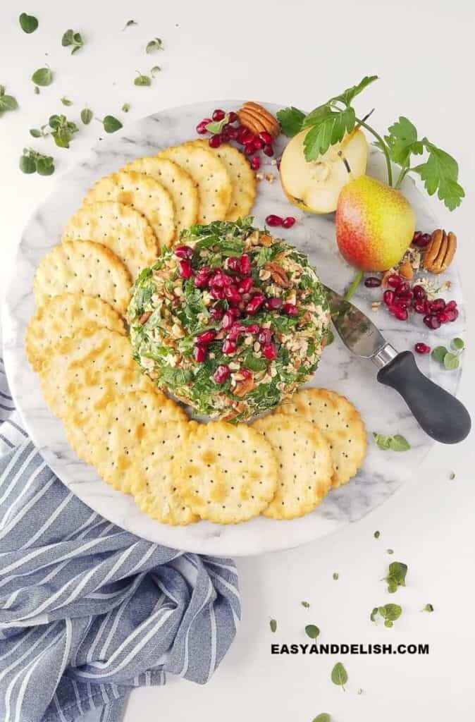 Cheese ball rolled in nuts and green garnish with pomegranate seeds on top and crackers layered around it and a pear.