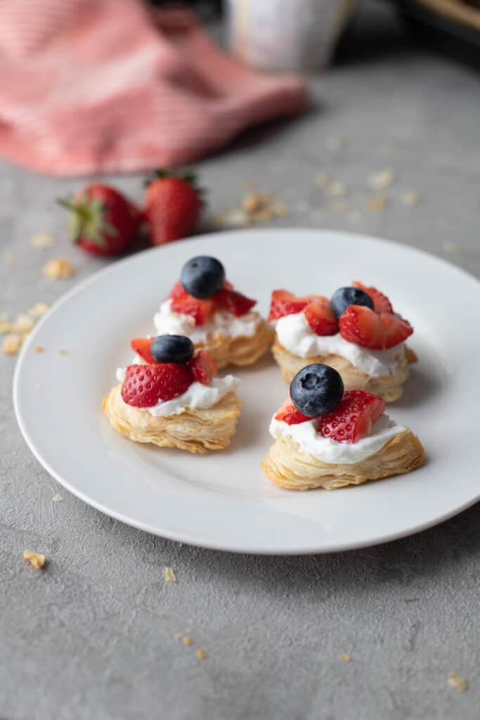 Puff pastry bites with whipped cream and fruit on top laying on round white plate with strawberries in the background.