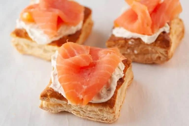 Squares of puff pastry topped with a herbed cream cheese layer and a piece of salmon on top.