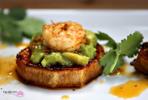 A slice of sweet potato with guacamole and a cooked shrimp on top drizzled with sauce.