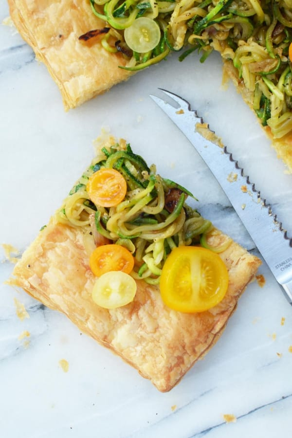 A square of puff pastry with zucchini spirals and cherry tomatoes on top with a knife laying next to it.
