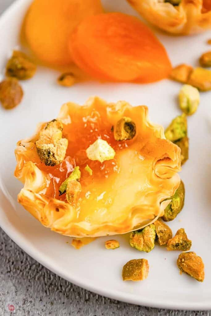 Close up of a Apricot, Pistachio, and Brie bite with pistachio garnish on a white plate with dried apricots in the background.