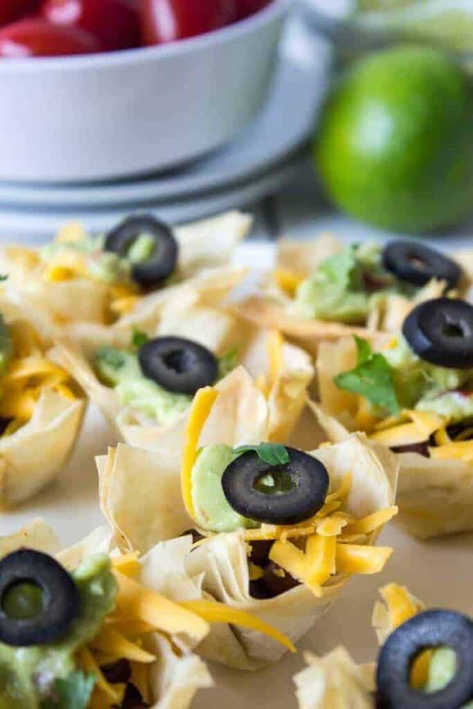 Close up of a Black Bean Taco cup with guacamole and shredded cheese with a slice of black olive on top.