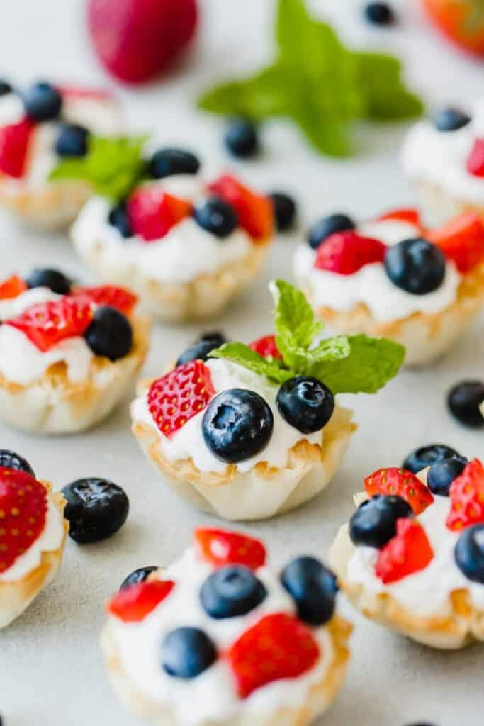 Greek yogurt fruit bites with blueberries and strawberries on top and a sprig of mint as a garnish.