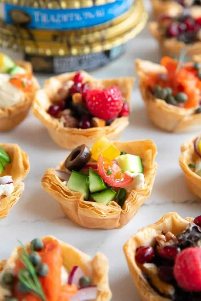 Phyllo cups filled with avocado, cherry tomatoes, cucumber, hummus, and a black olive.