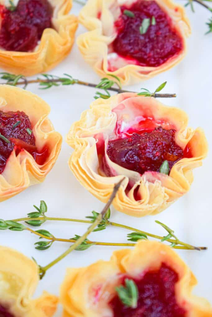 A close up of a phyllo cup filled with melted brie with cranberry sauce on top with fresh thyme laying next to it.