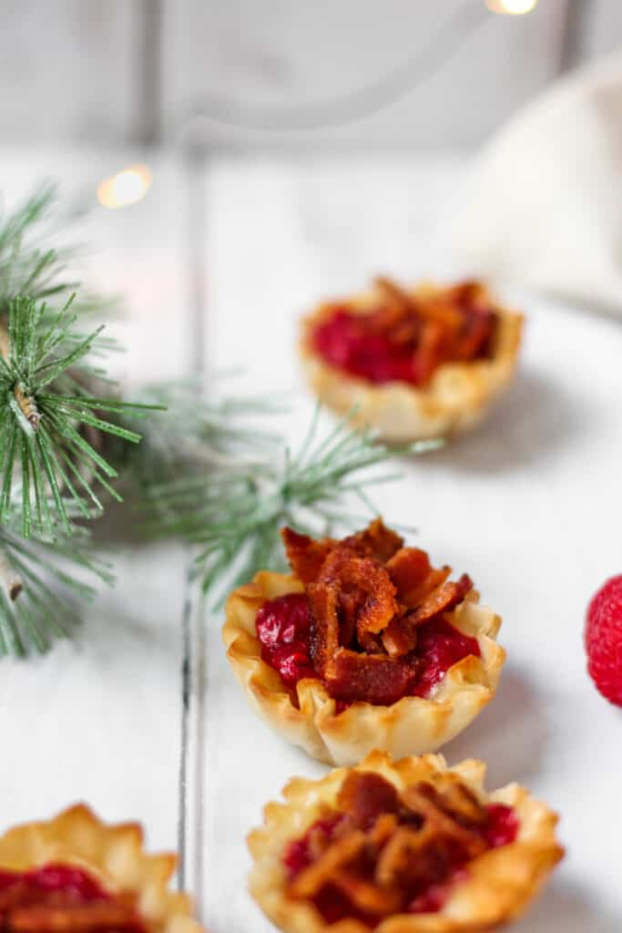 Phyllo cups filled with brie, raspberry jam and bacon with a pine branch in the background.