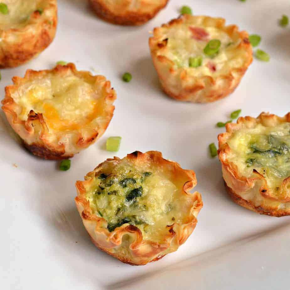 Four mini quiche on a white surface and garnished with green onions.