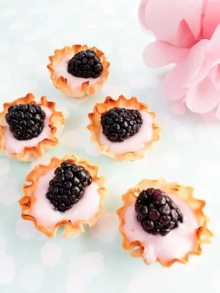 Five blackberry yogurt tarts with a pink flower in the corner.