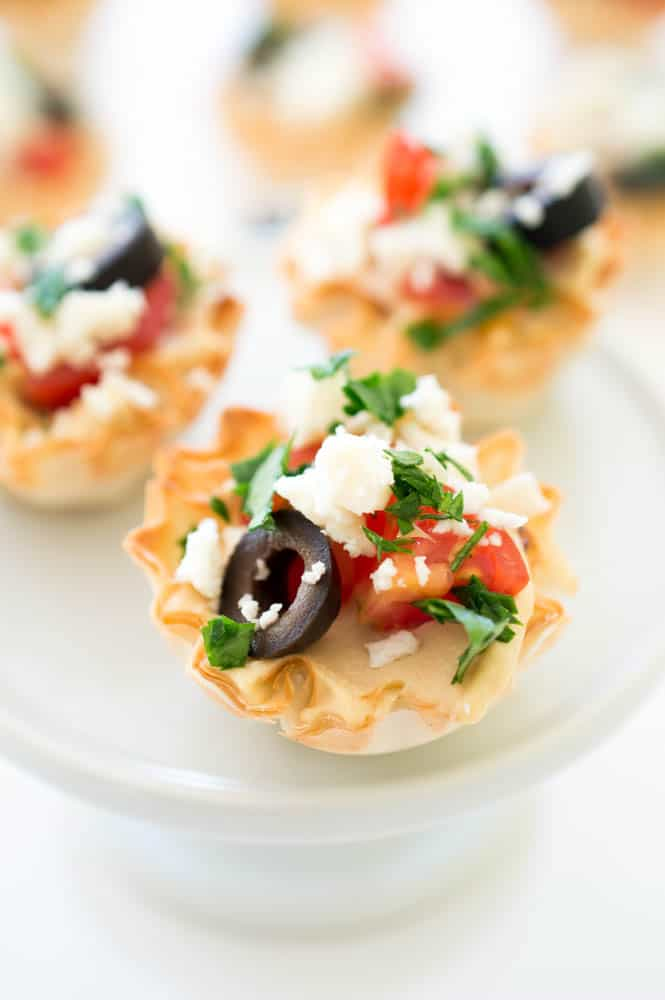A close up of a Greek hummus phyllo bite with a black olive, tomato, feta cheese and basil on top.