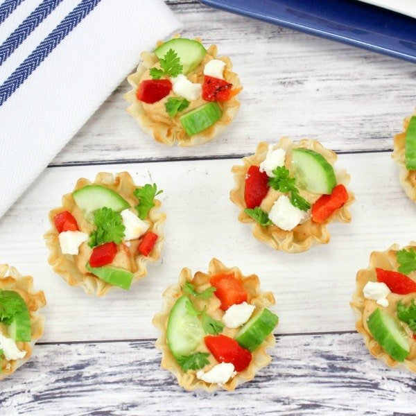 Phyllo cups filled with hummus and topped with cucumber, cheese and red pepper on a wood look background.