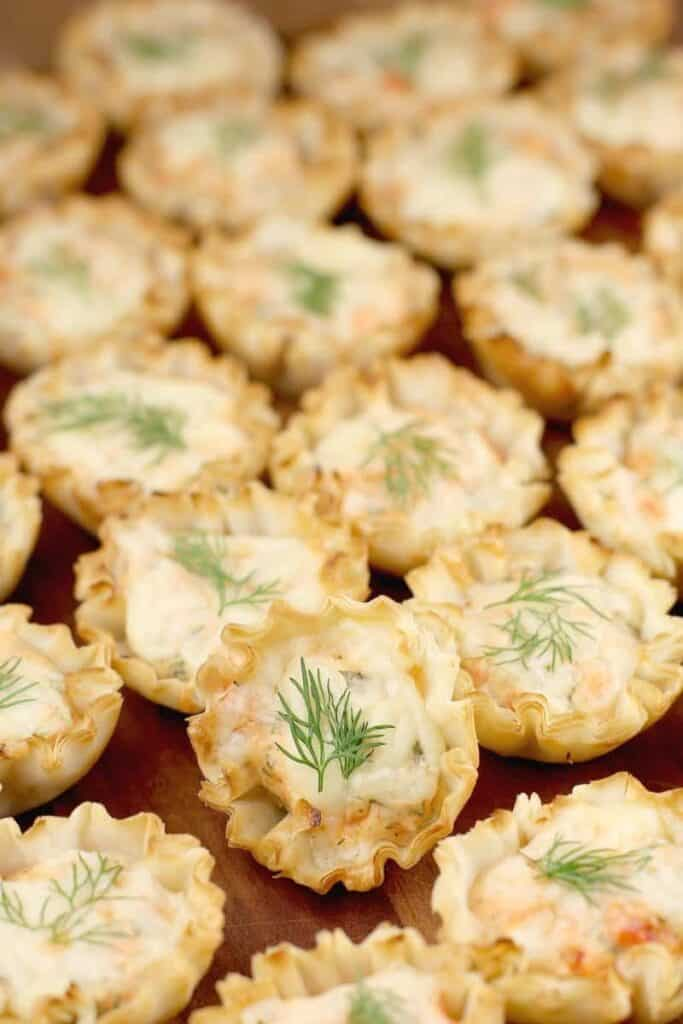 Rows of Smoked Salmon Mini Tarts garnished with a sprig of fresh dill.