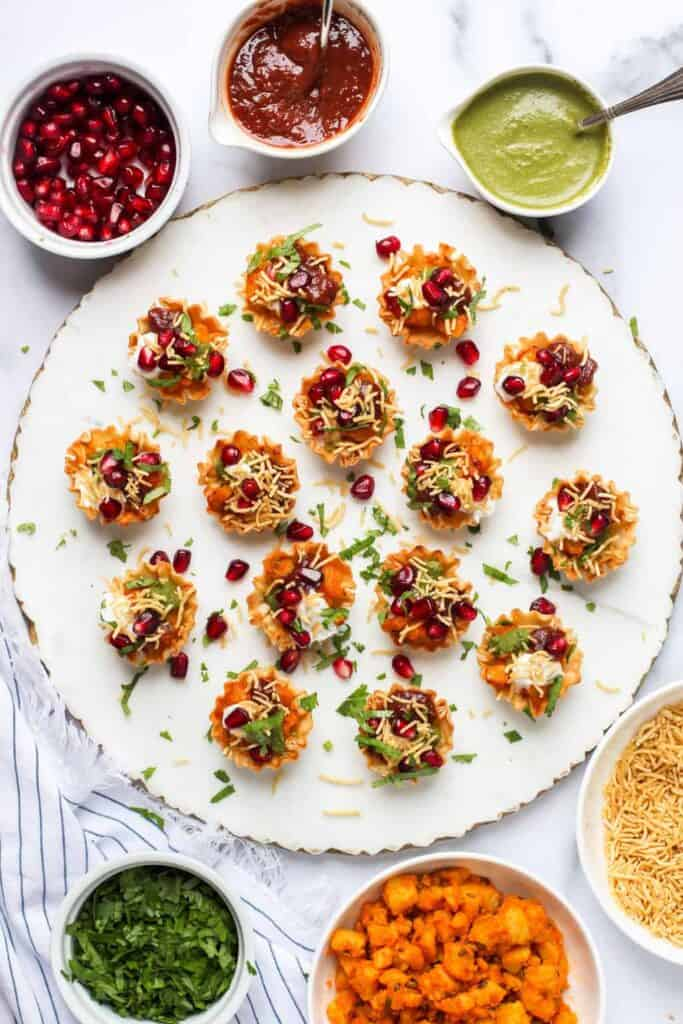 A round tray of Aloo Chaat in Phyllo Cups garnished with pomegranate seeds and cilantro.