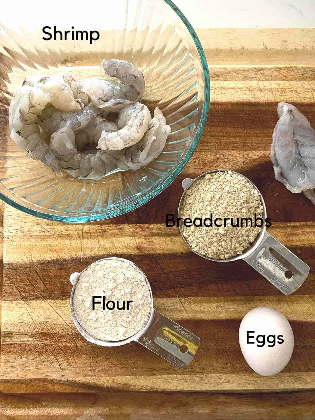 Ingredients to make butterflied shrimp on cutting board.