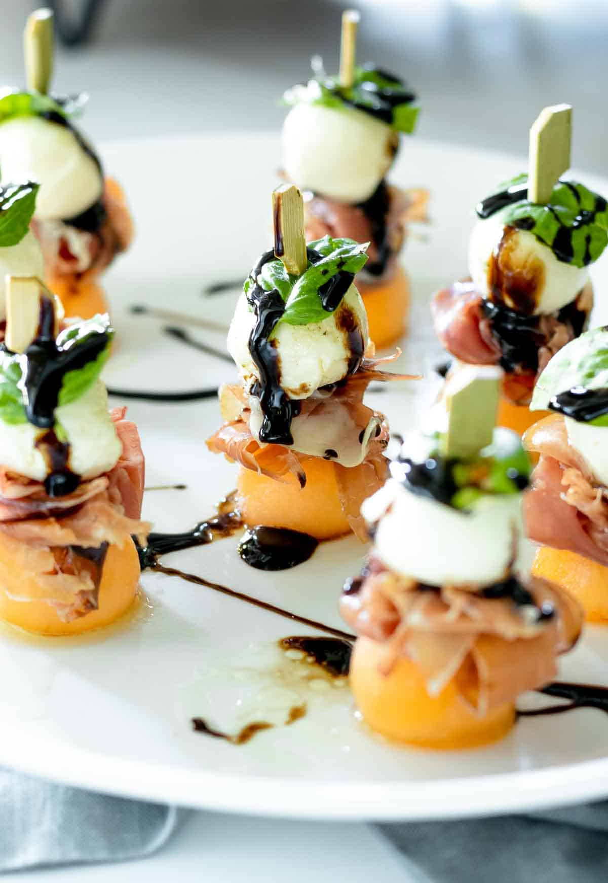 Mozzarella prosciutto and melon skewers with balsamic glaze on a white plate.