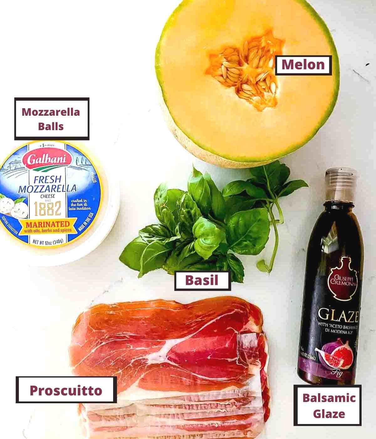 Prosciutto, basil balsamic, mozzarella and melon on a table.