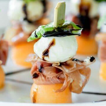Prosciutto melon mozzarella skewers on a plate drizzled with balsamic glaze.