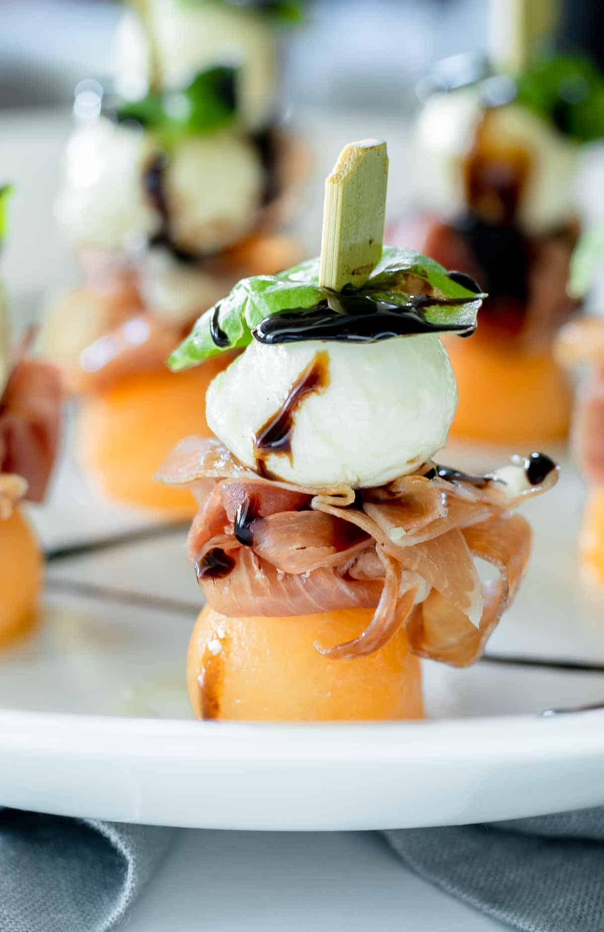 Melon, prosciutto and mozzarella skewers standing up with balsamic vinegar glaze.