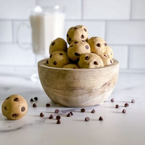 Edible no bake chocolate chip cookie dough balls stacked in a bowl with chips sprinkled on table.