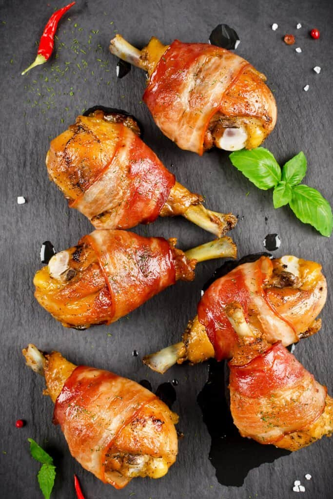 Bacon wrapped chicken legs on a black surface with green leaf garnish.