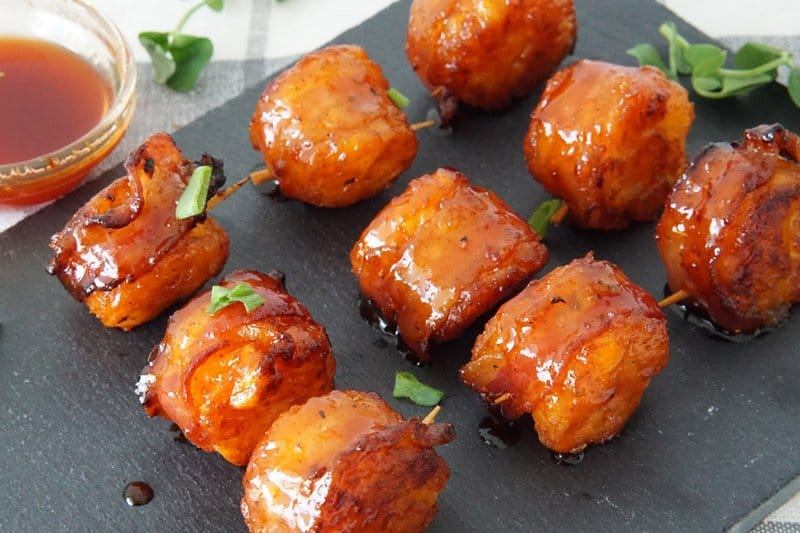 Bacon wrapped tater tots with sriracha honey glaze on a black cutting board with a green leaf garnish and a small bowl of sauce next to them.