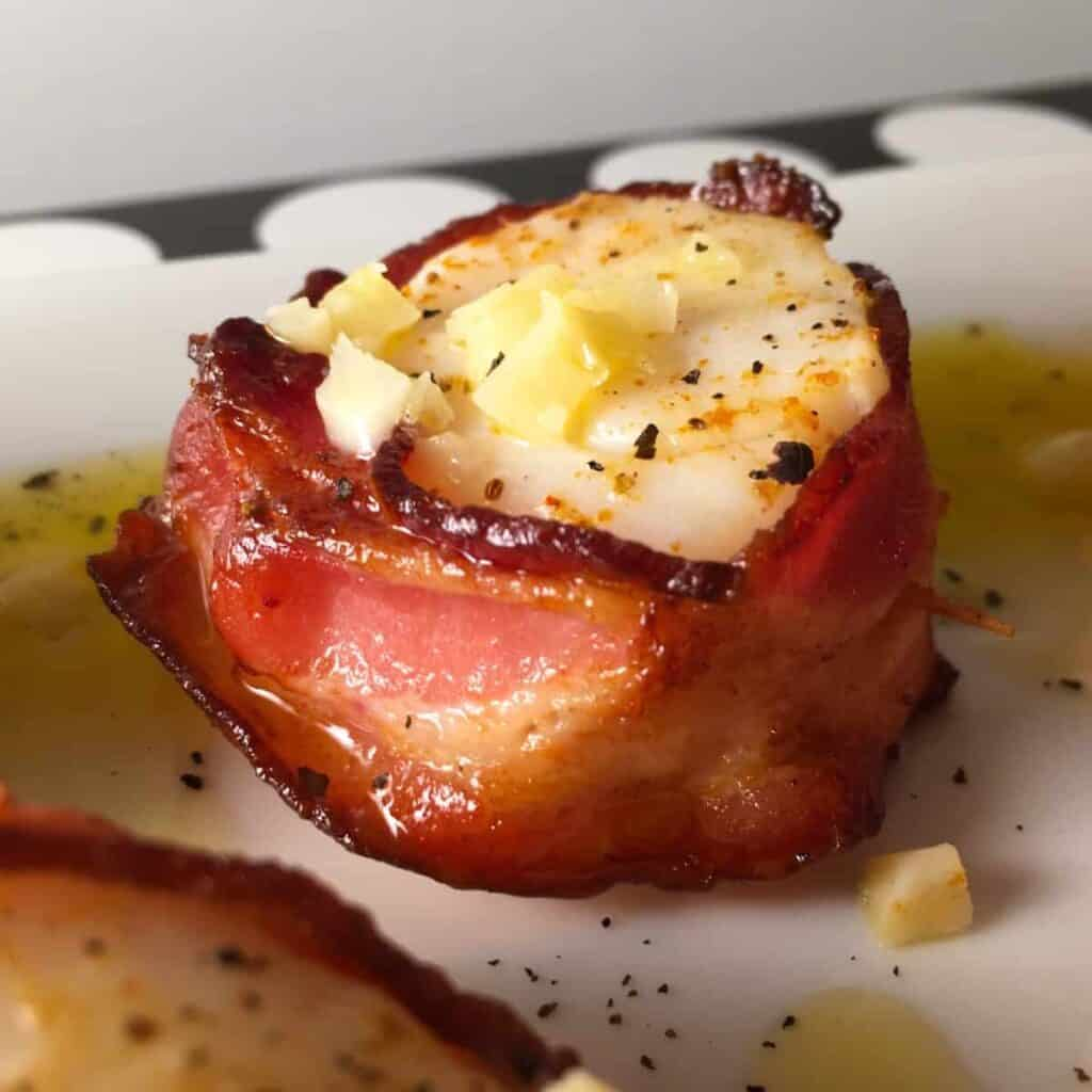 A close up of a bacon wrapped scallop on a white surface drizzled with garlic butter.