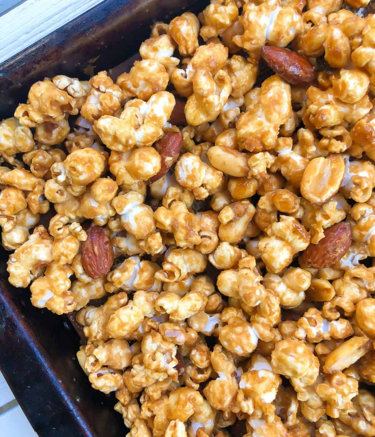 Closeup of caramel popcorn with peanuts and almonds on a baking sheet.