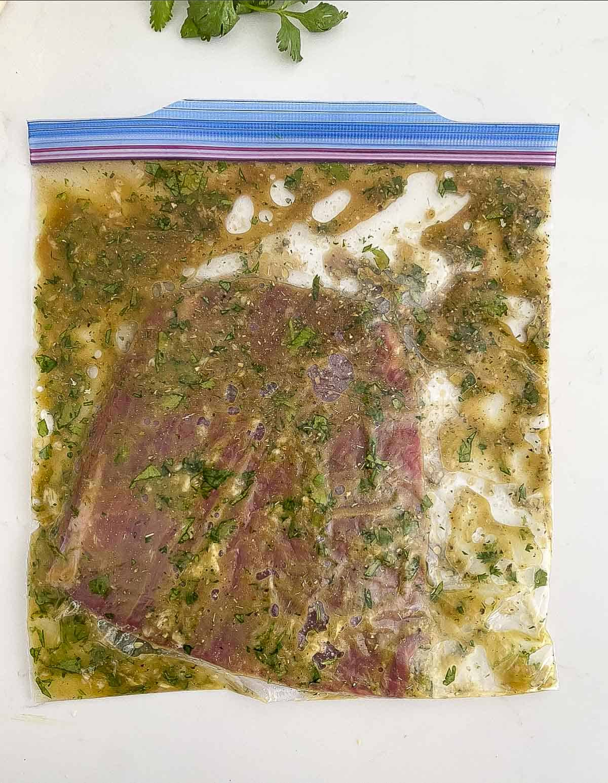 Flank steak with carne asada marinade in a plastic bag.