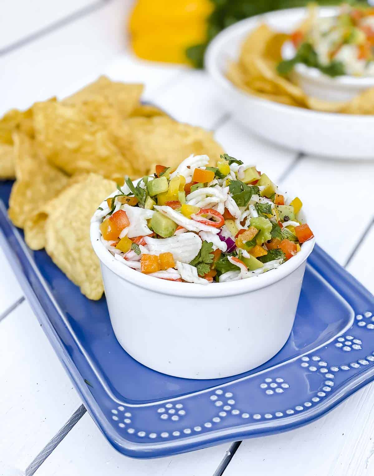 Imitation crab ceviche in a white bowl with tortilla chips on serving tray.